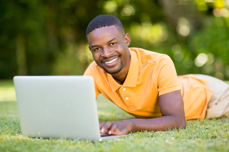 solitariness: Happy man using his laptop at park