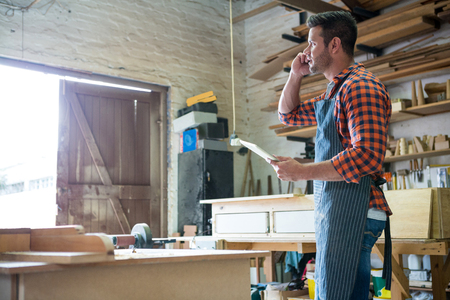 carpenter's bench: Carpenter calling someone in a dusty workshop