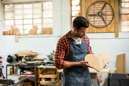 carpenter's bench: carpenter looking at his craft in a dusty workshop