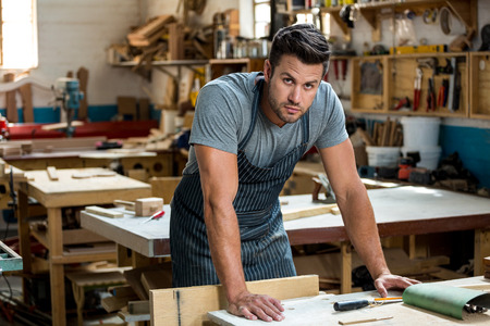 carpenter's bench: Carpenter is posing in a dusty workshop