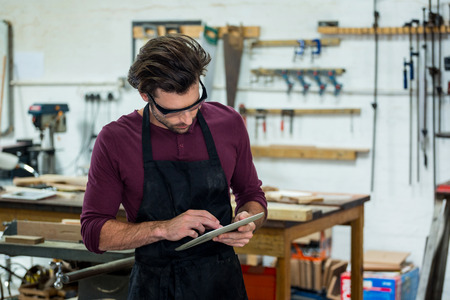 carpenter's bench: carpenter is using his tablet