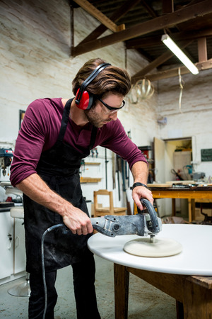 earing: Carpenter working on his craft in a dusty workshop