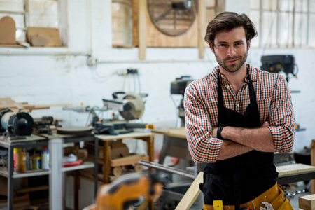 carpenter's bench: Carpenter is posing with his craft in a dusty workshop Stock Photo