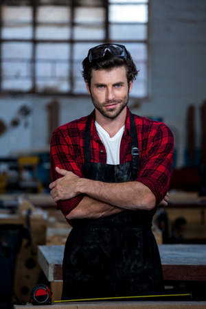 crossing arms: Carpenter smiling and crossing arms on his workshop Stock Photo