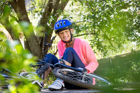 Senior woman is hurting because of her bike in a forest