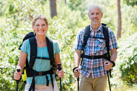 adventuring: Senior couple standing with their stick in a forest