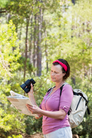 adventuring: senior woman is reading in a forest