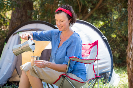 adventuring: senior woman is sitting beside her tent in a forest Stock Photo