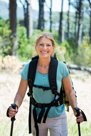adventuring: senior woman standing with their stick in a forest Stock Photo