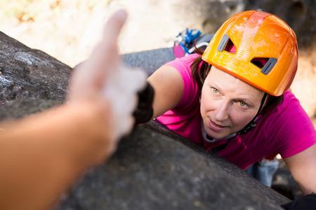 abseiling: Man helping woman in rock climbing