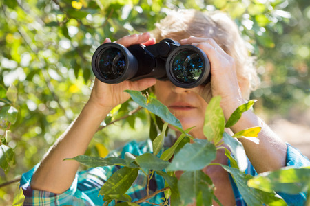 inquiring: Close up of a woman looking on binoculars on the wood