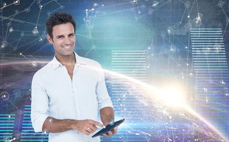 man using computer: Portrait of smiling man using tablet computer against hologram background