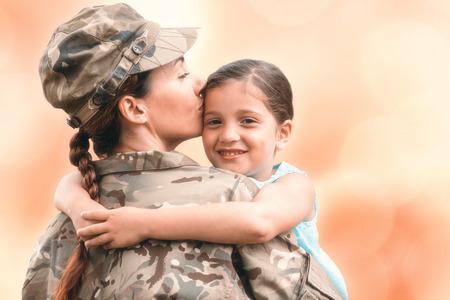Primer plano de la madre en el ejército hija uniforme besos contra el fondo colorido
