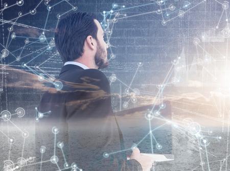mid adult men: Businessman in suit holding laptop against hologram background