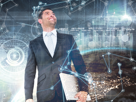 Businessman looking up holding laptop against image of a earth