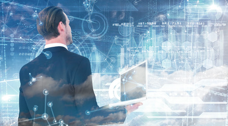 well dressed: Businessman looking up holding laptop against hologram background Stock Photo