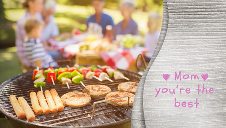 mid adult men: Mothers day greeting against happy family eating barbecue Stock Photo