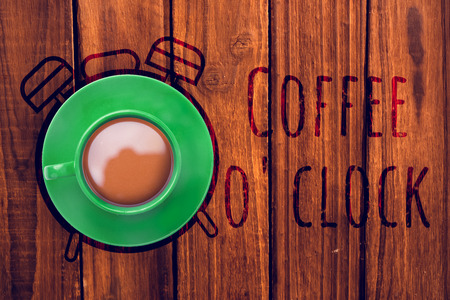 Green cup of coffee against overhead of wooden planks