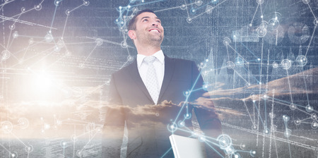 looking up: Businessman looking up holding laptop against hologram background Stock Photo