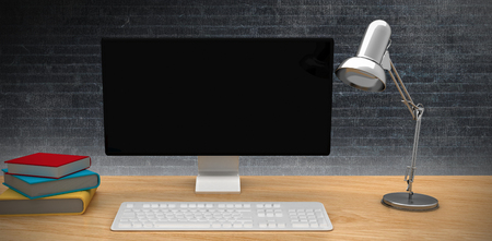 bulding: A computer over a desk  against a dark wall
