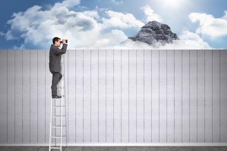 using binoculars: Businessman standing on ladder using binoculars against mountain peak through the clouds Stock Photo