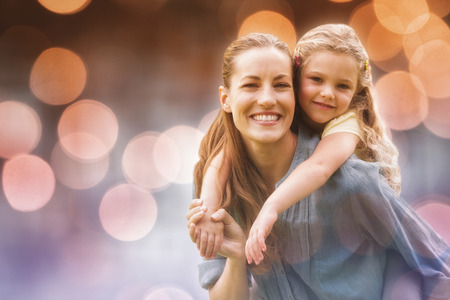 carrying girl: Glowing background against portrait of woman carrying girl at park