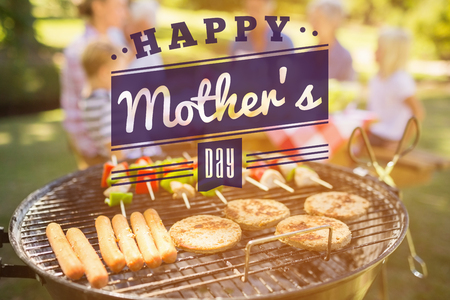 mid adult men: mothers day greeting against happy family eating barbecue