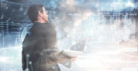 mid adult men: Businessman looking up holding laptop against hologram background Stock Photo