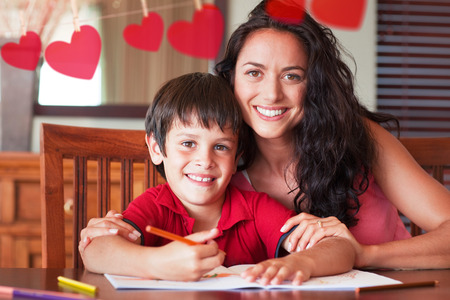Happy mother helping his son for homework against hearts hanging on a line photo