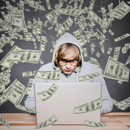 intruding: Man in hood jacket hacking a laptop against grey background Man in hood jacket hacking a laptop on black background
