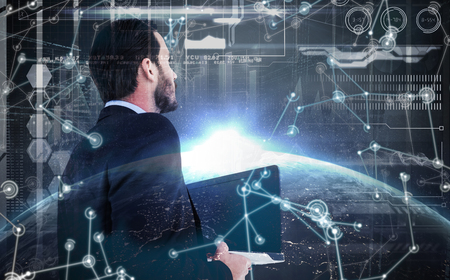 well dressed: Businessman in suit holding laptop against image of a earth