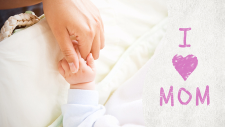 Mothers day greeting against a mother holding her baby hand photo