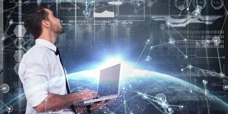 sophisticated: Sophisticated businessman standing using a laptop  against image of a earth Stock Photo