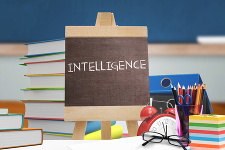 higher intelligence: Intelligence word against red apple on pile of books in classroom
