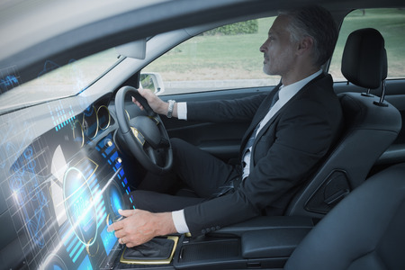 drivers seat: Technology car interface against handsome businessman in the drivers seat Stock Photo