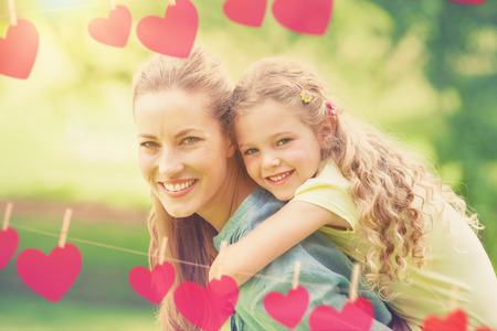 carrying girl: Hearts hanging on a line against side view of a woman carrying girl at park Stock Photo