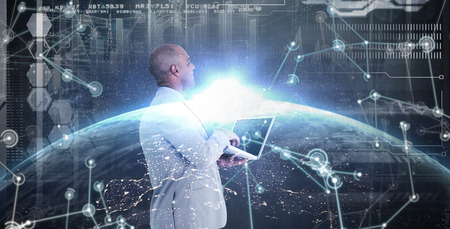 using laptop: Businessman using laptop against image of a earth