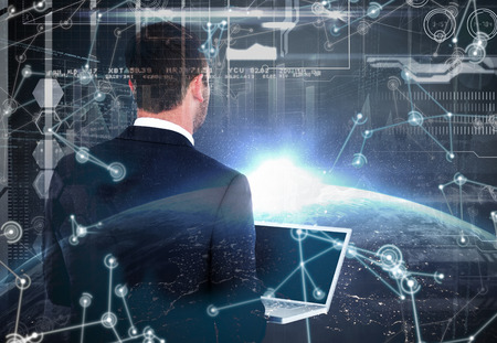 mid adult men: Businessman looking up holding laptop against image of a earth