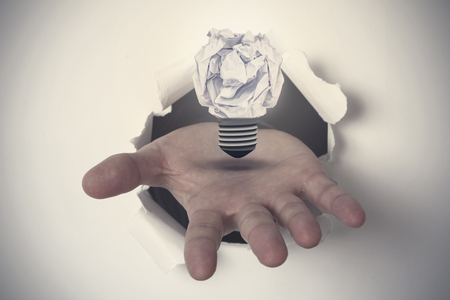 which one: Hand ripping through paper against  five bulbs which one is in the process of function Stock Photo