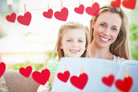 one parent: Hearts hanging on a line against happy family posing together