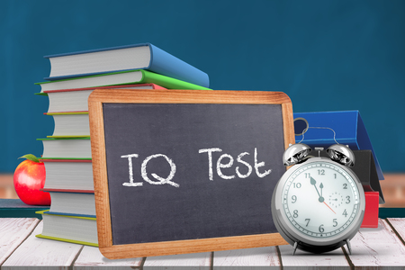 iq: Word IQ TEST against red apple on pile of books in classroom