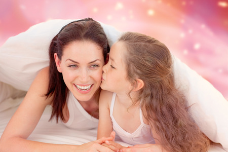 Mother and her daughter having fun on bed against glowing background photo