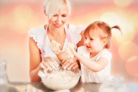 Simper woman baking cookies with her daughter against background of multiple color photo