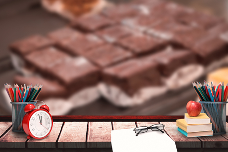 indulgent: School supplies against display of fresh and delicious slices of brownies