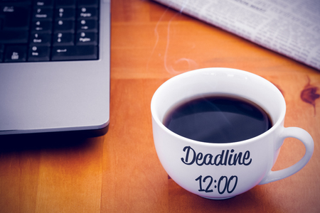 faience: Deadline sentence against a cup of coffee with a laptop and a newspaper