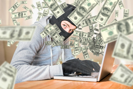 thievery: Focused thief with hood typing on laptop against light shining into living room Stock Photo