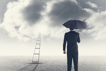 sheltering: Rear view of businessman sheltering with umbrella against cloudy sky background
