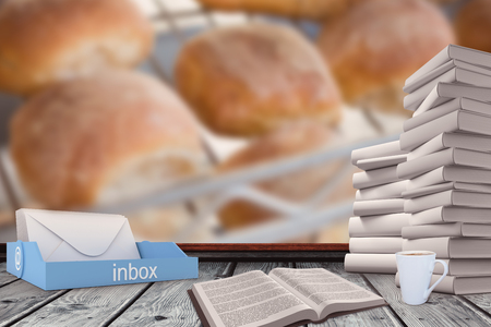 freshly: An inbox beside books against freshly baked rolls on rack Stock Photo