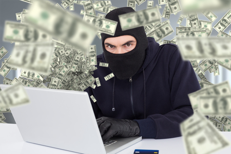Hacker in balaclava hacking a laptop against digitally generated room with window and doors Stock Photo