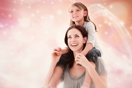 Cheerful mother giving piggyback ride to her daughter  against glowing background photo
